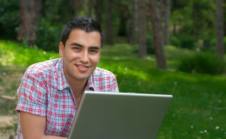 typewrite: Smiling young man sitting in a forest and using a laptop