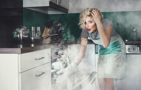 Creative photo of a astonished woman cook frying lunch in a oven. Smoke, vapor around in the kitchen or home