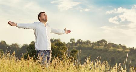 自由。両手で草を歩く若い男。春 - 秋の時間を楽しんでください。 写真素材