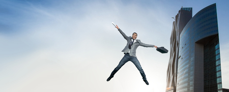 Businessman jumping in joy. Full length of smart happy man holding briefcase in the air. outdoors Banco de Imagens