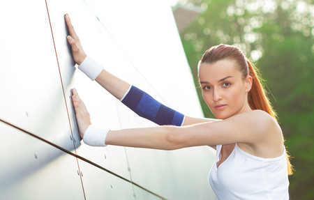 Stretching athlete female warming up for a workout outdoors. Healthy fitness lifestyle