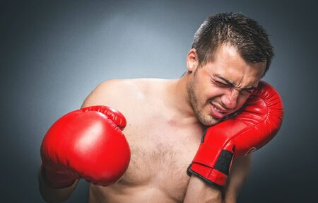 Boxer feel hurt and pain, knockout situation. Dark gray background. Beaten fighter with red sport boxing gloves. Waist up of defeated kickboxer