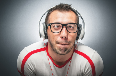 Young man make a funny face. Young freak guy with headphones and facial expression - grimace over dark gray background