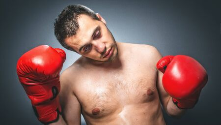 Close up of knockout boxer over dark gray background. Comic weak fighter with red sport boxing gloves. Waist up humorous kickboxer