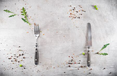 Blank gray stoned table with dishes fork and knife. Food invitation. Ready to serve and cook fresh meal. Copy empty space. Top view - flat lay