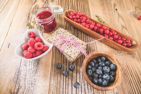 Pastry appetizers with blueberries, currant and raspberries serving on wooden table Stock Photo