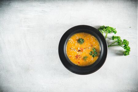 Vegetable soup on gray kitchen table. Served healthy food or lunch in a bowl. Top view. Copy space for text