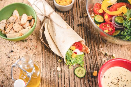 Tortillas wraps with chicken and vegetables on wooden table. Imagens
