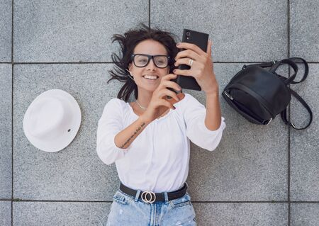 Smiling happy woman with smarthphone browsing internet, or making selfie, above view
