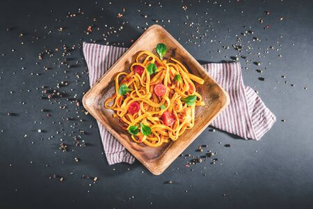 Plate of pasta with tomato sauce over dark table. Served portion of delicious tagliatelle. Isolated on black