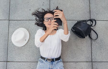 Young happy girl with smarthphone browsing, above view