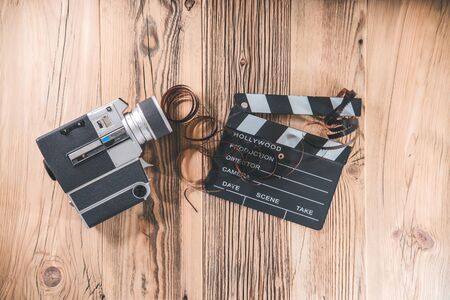 Vintage camera with clapperboard and filmstrip on wooden table with copyspace for text. Retro cinema concept