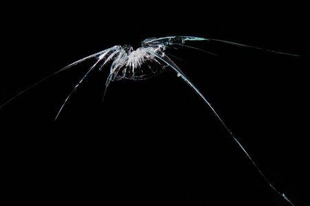 Cracked glass, isolated on black background. Studio shot