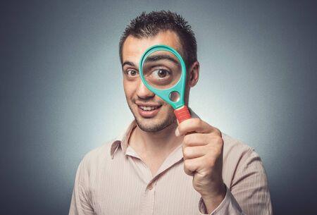 Funny man with magnifier looking, big eye, dark gray background. Studio shot Stockfoto