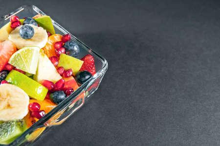 Fruit salad in a glasses bowl on dark gray black table Archivio Fotografico