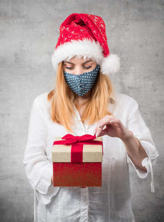 Thoughtful Santa woman with christmas gift isolated on gray background. Young girl wearing red santa hat and holding present box. Studio shot