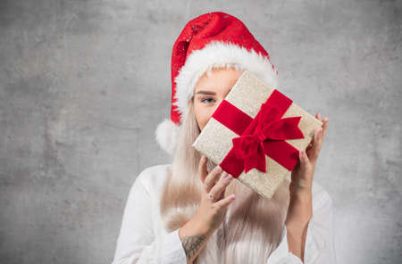 Surprised beautiful blond woman with wears christmas santa claus hat - cap and holding red gift box - present with ribbon, isolated on gray background. Studio shot