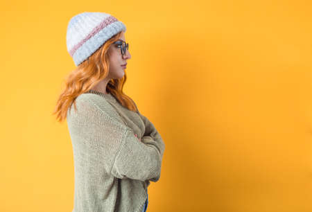 Side view of young woman with crossed arms standing, Profile of beautiful girl looking to copy space, isolated on yellow background. Studio shot 免版税图像