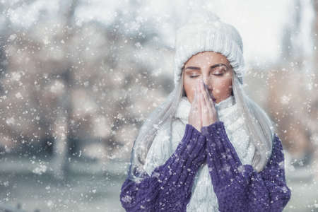 Young woman warming her hands, wearing warm clothing on snowing winter day outdoors. Cute girl feeling cold.Copy space for text. Winter concept.