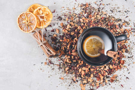 Fruit tea with cinnamon and dried orange in a cup - teacup on gray table. Top view, overhead