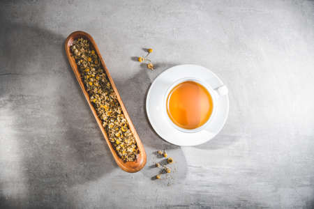 Chamomile tea cup with loose flowers or dried petals on the gray table. Top view - above Blank free space for your advertising or text. Copyspace