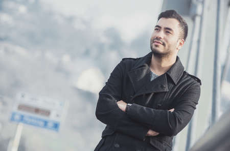 Serious handsome young turk man with crossed arms. Outdoors, outside. Blurred background, copyspace