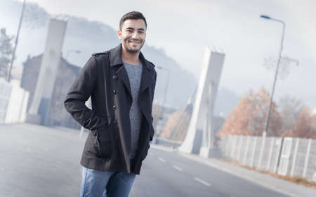 Man standing in street. Guy in coat, cold weather. Autumn morning, outdoors. Copyspace
