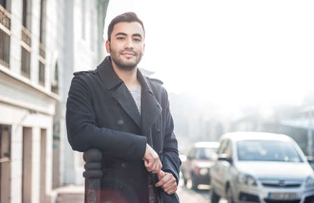 Gorgeous young man looking outdoors. Handsome beautiful guy posing outside. Urban scene. Copyspace