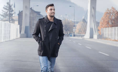 Young man walking on street, autumn or winter cold day. Outdoors, outside. Gorgeous guy in coat