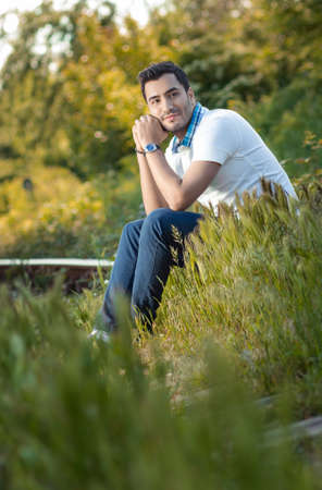 Man sitting on grass in forest Happy guy relaxing on meadow. Daylight, outdoors