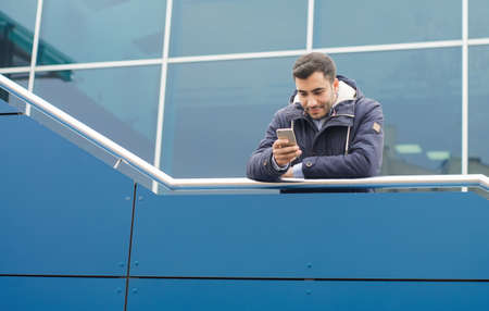 Man typing on mobile phone and wearing winter jacket, outdoor - outside