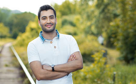 Portrait of a young smile man with crossed arms. Close up of a gorgeous guy, outdoors