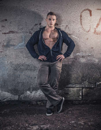 Bodybuilder standing over wall. Handsome guy showing his musle, copyspace for text
