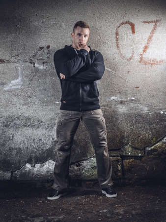 Gorgeous young man standing against wall, dark indoor, full length