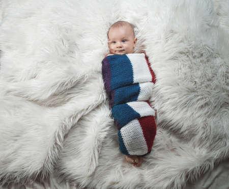 Cute baby boy on bed, studio shot