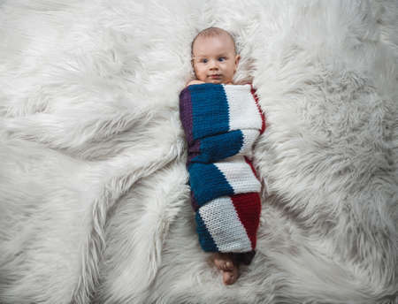 Baby boy on bed, studio shot. Above view
