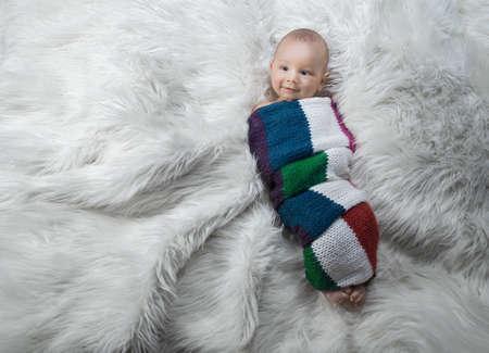 Lovely baby boy on bed, studio shot