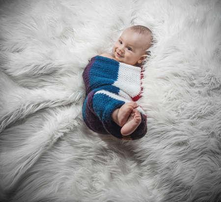 Baby boy lying on fur, studio shot