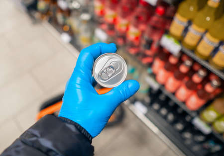 Buying supplies at nutrition during virus. Close up hand with product in supermarket Stock Photo
