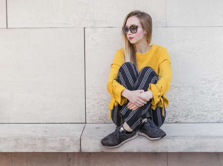 Young girl sitting against wall, outside. Trendy woman with sunglasses with crossed legs and arms