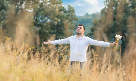 Man standing in big grass with raised arms. Freedom - wellbeing concept. Outdoors