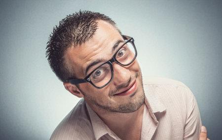 Funny man looking to you. Nerd guy with eyeglasses watching, Dark gray background. Studio shot