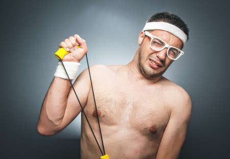 Funny man exercising over dark gray background. Nerd guy with eyeglasses holding expander. Close up of silly young man doing aerobics. Studio shot Banque d'images