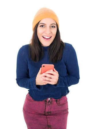 Excited young woman reading good news on mobile phone, isolated on white background. Surprised trendy girl holds smarthphone. Studio shot