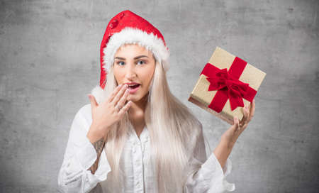 Surprised beautiful blond woman with wears christmas santa claus hat - cap and holding red gift box - present with ribbon, isolated on gray background. Studio shot Stock Photo