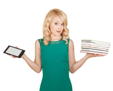 the beautiful, slender blonde compares a tablet and books photo