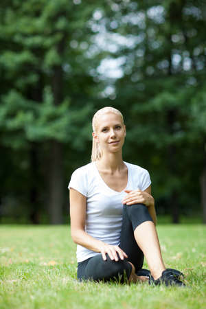 The beautiful blonde stretching outdoors photo