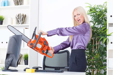 pissed: beautiful girl at the office cuts the monitor with a chainsaw Stock Photo