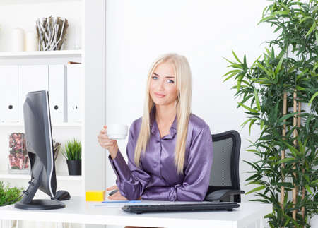 Cheerful female having a coffee break in the office photo