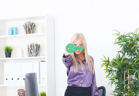 young woman at office holds big a green key photo